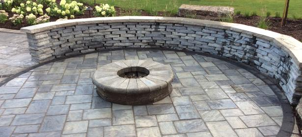 Unilock rivercrest seat wall (Costal Slate) with firepit made from Unilock Brussels Dimensional Stone & Fullnose coping (Sierra) with circular Richcliff (Dawn Mist) patio
