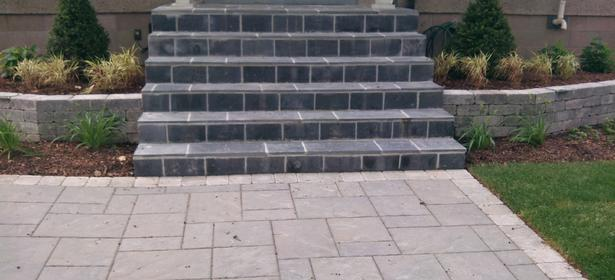 Black Limestone Flagstone installed on existing concrete steps plus a Unilock Beacon Hill Flagstone (Granite) walkway with a Unilock Brussels Block (Limestone) border